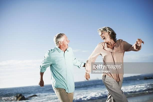 Playful senior couple running on beach