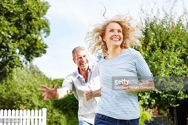 Juguetón senior hombre corriendo detrás de mujer madura: al aire libre