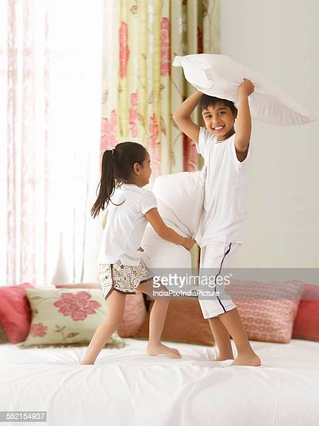 Playful siblings having pillow fight on bed