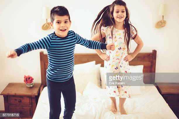 Playful siblings jumping on the bed