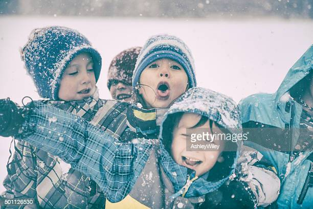 Playful silly children enjoy the snow on a stormy day