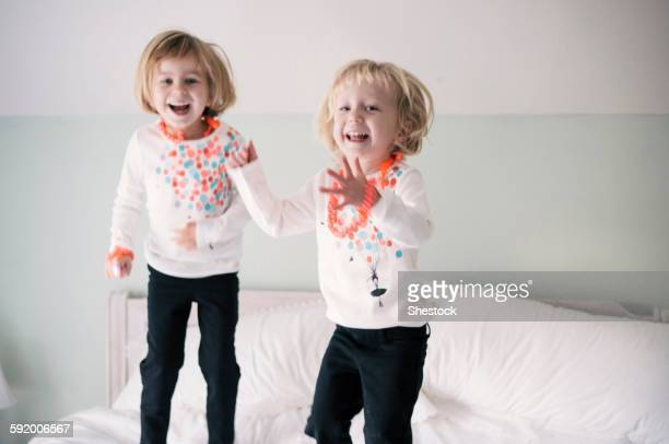 Playful sisters jumping on bed