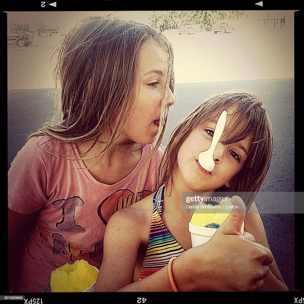 Playful sisters teasing while eating ice creams outdoors