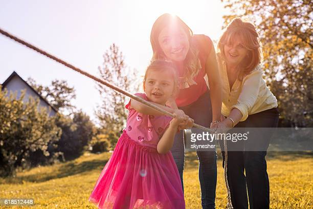 Playful small girl pulling rope with her mother and grandmother.