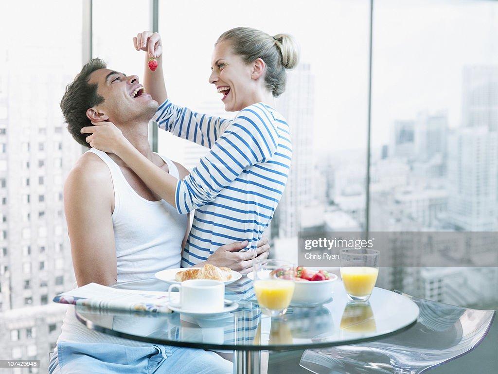 Playful woman feeding strawberry to husband at breakfast : Stock Photo