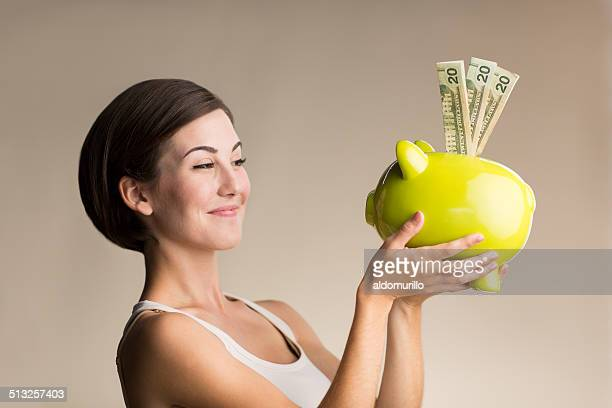 Playful woman holding piggy bank with dollars