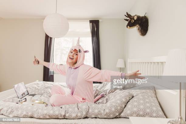Playful woman in unicorn costume in bedroom