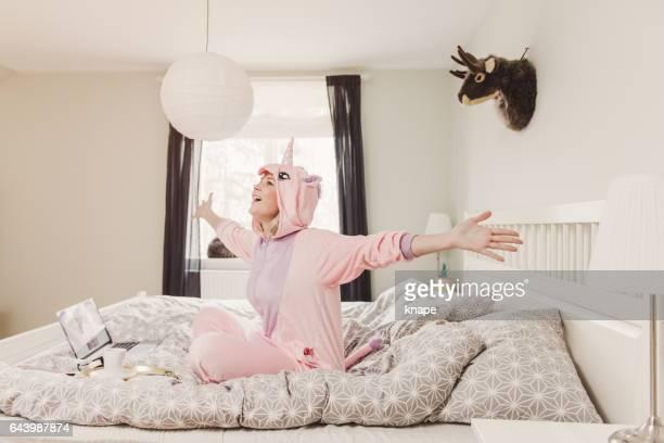 Verspielte Frau im Einhorn Kostüm im Schlafzimmer