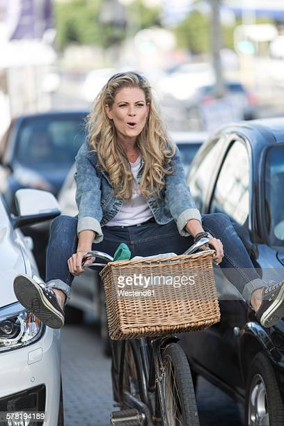 Playful woman on bicycle in traffic jam