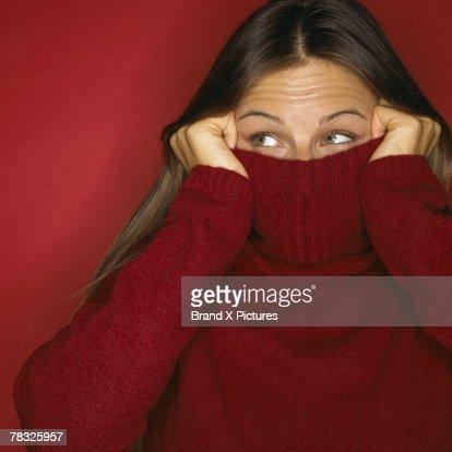 Playful woman peeking out of turtleneck : Stock Photo