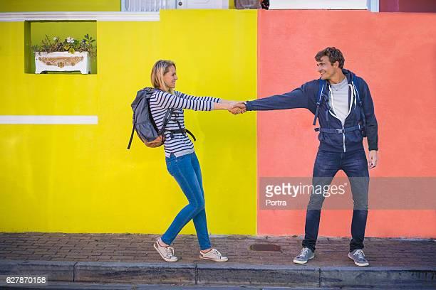 Playful woman pulling man at sidewalk against wall