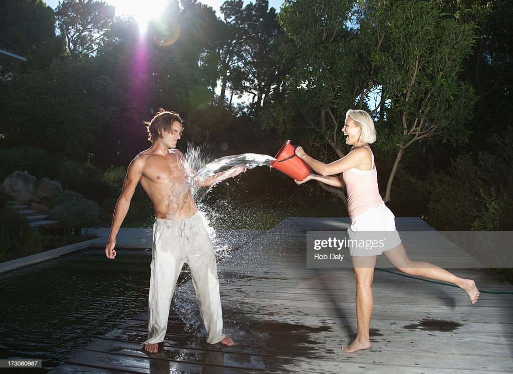 Playful woman throwing bucket of water on boyfriend : Stock Photo