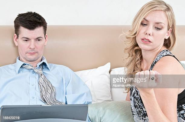 Playful woman with man trying to work on laptop (IV)
