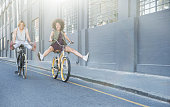 Playful women coasting on bicycles down urban street
