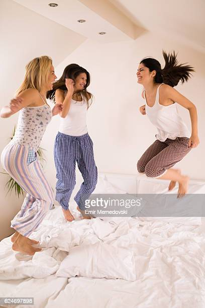 Playful women having fun at slumber party jumping on bed