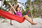 Playful women with hammock on beach