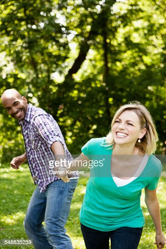 Playful young couple in a park : ストックフォト