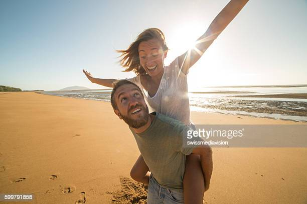 遊び心のある若いカップルはビーチサンセットに