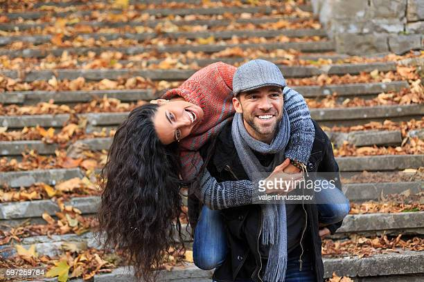 Playful young couple standing on stairs and having fun