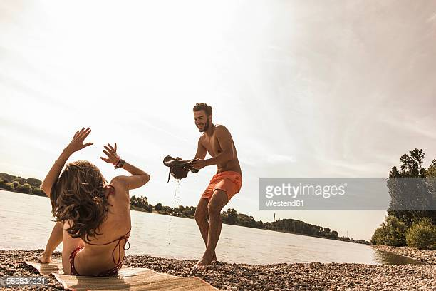 Playful young man trying to pour water over girlfriend sunbathing by the riverside