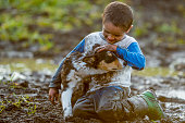 An elementary age boy is playing outside in the mud with his pet puppy. The little boy and the dog are covered in mud.