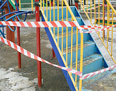 A playground  with a warning tape around, cropped outdoor shot, concept of a danger