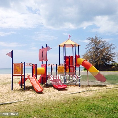 Playground Equipment On Grassy Field By Sea Against Cloudy Sky