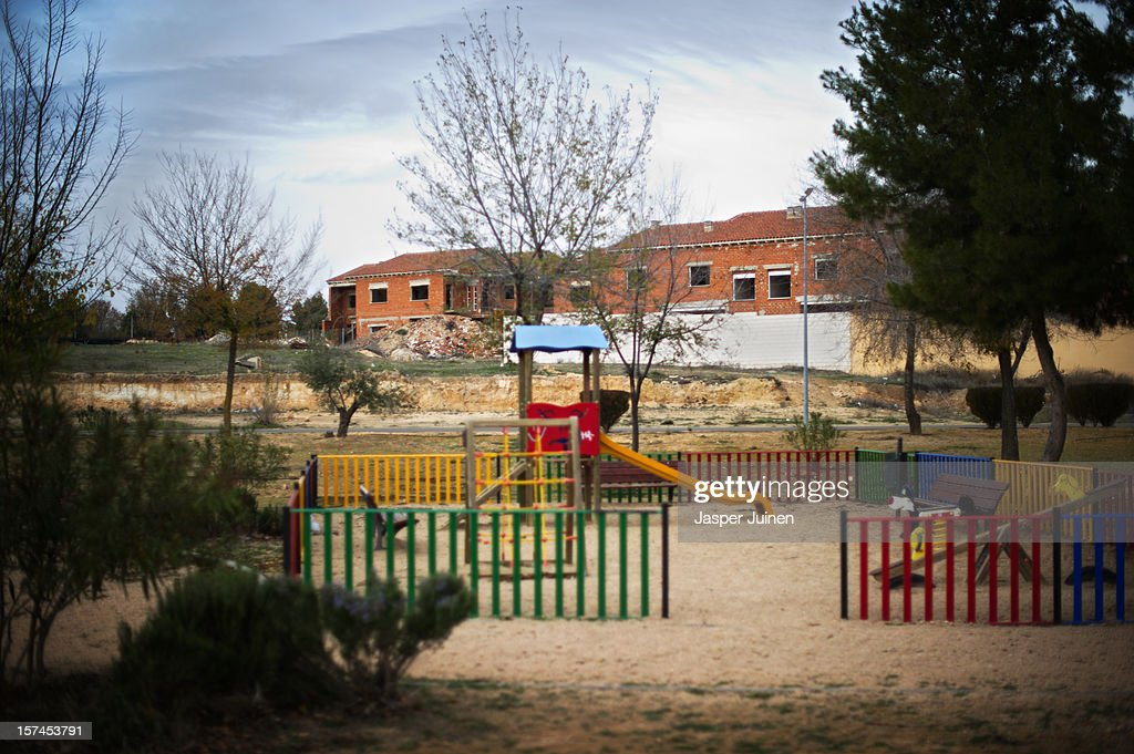 A playground for children stands backdropped by unfinished homes on November 30, 2012 in Villacanas, Spain. During the boom years, where in its peak Spain built some 800,000 houses a year accompanied by the manufacturing of millions of wooden doors, the people of Villacanas were part of Spain's middle class enjoying high wages and permanent jobs. During the construction boom years the majority of the doors used within these new developments were made in this small industrial town. Approximately seven million doors a year were once assembled here and the factories employed a workforce of almost 5700 people, but the town is now left almost desolate with the Villacanas industrial park now empty and redundant. With Spain in the grip of recession and the housing bubble burst, Villacanas is typical of many former buoyant industrial Spanish towns now struggling with huge unemployment problems.