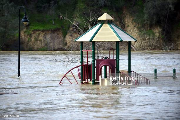 A playground is seen submerged in flowing water at Riverbend Park as the Oroville Dam releases water down the spillway in Oroville California on...