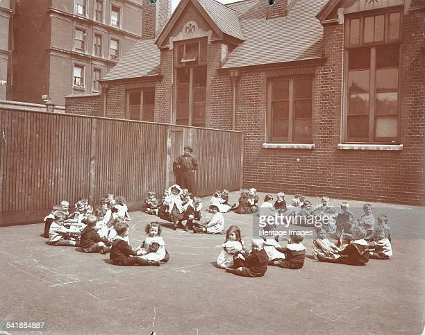 Playground scene Hugh Myddelton School Finsbury London 1906 Pairs of very young children play a seesaw game in the school playground The flats of the...