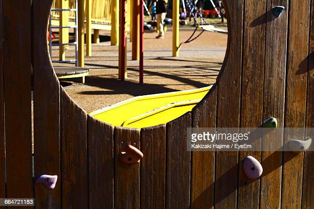 Playground Seen Through Hole On Wooden Fence