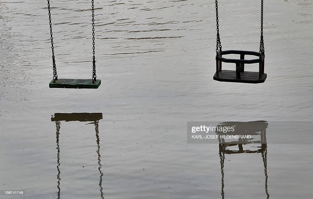 A playground with swings is flooded by the river Main on December 27, 2012 in Wuerzburg, southern Germany. Due to melting snow and rainfall, the Main burst its banks. AFP PHOTO / KARL-JOSEF HILDENBRAND GERMANY OUT