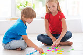 Two cute little children playing with plastic colorful letters while sitting on the hardwood floor