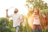 Young cheerful couple playing badminton in the park