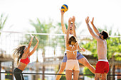 Four people having fun while playing volleyball. They are on the net.
