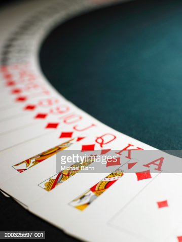 Playing cards spread out in arc, suit of diamonds in foreground : Stock Photo