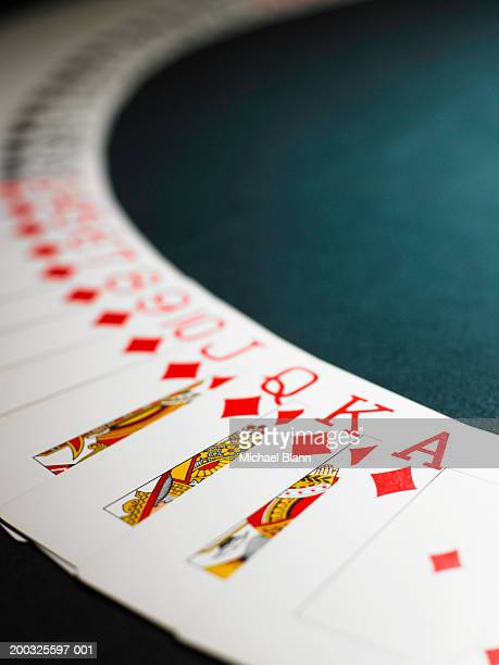 Playing cards spread out in arc, suit of diamonds in foreground