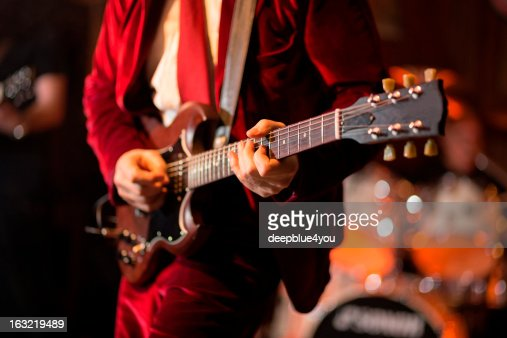 Playing electric guitar on stage : Stock Photo