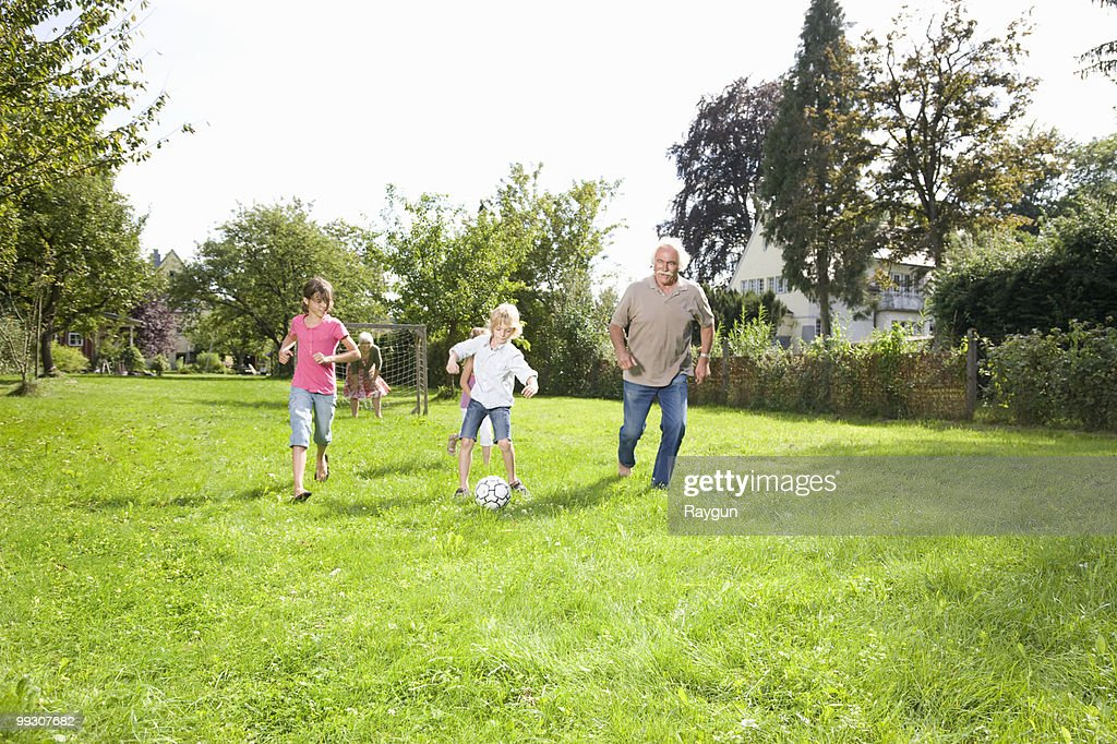 Playing football with the grandparents : Stock Photo
