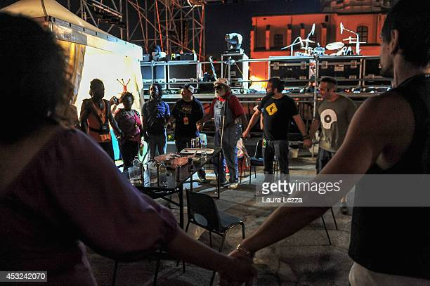 Playing for Change band and fans are seen in the backstage holding hands to form a circle before they perform on stage on August 5 2014 in Livorno...