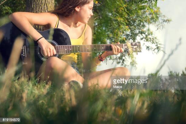 Jouer de la guitare au coucher du soleil