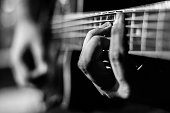 Guy playing acoustic guitar. Black and white colors and hand focused.