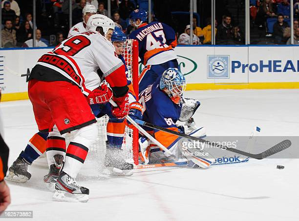Playing his first game of the season Kevin Poulin of the New York Islanders defends the net against Chad LaRose of the Carolina Hurricanes at Nassau...