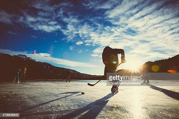Juego de hockey sobre el hielo del lago helado en la puesta de sol.