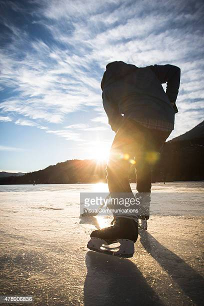 Playing ice hockey on frozen lake in sunset.