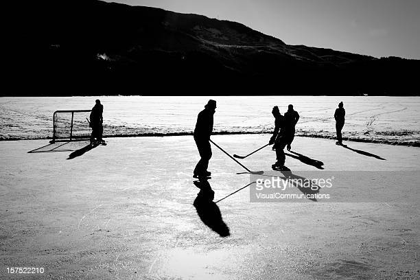 Playing ice hockey on frozen lake.