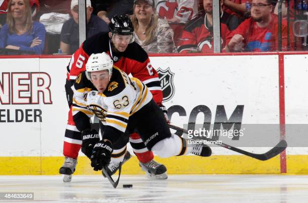 Playing in his 300th NHL game Brad Marchand of the Boston Bruins is upended by Andy Greene of the New Jersey Devils during the second period at the...