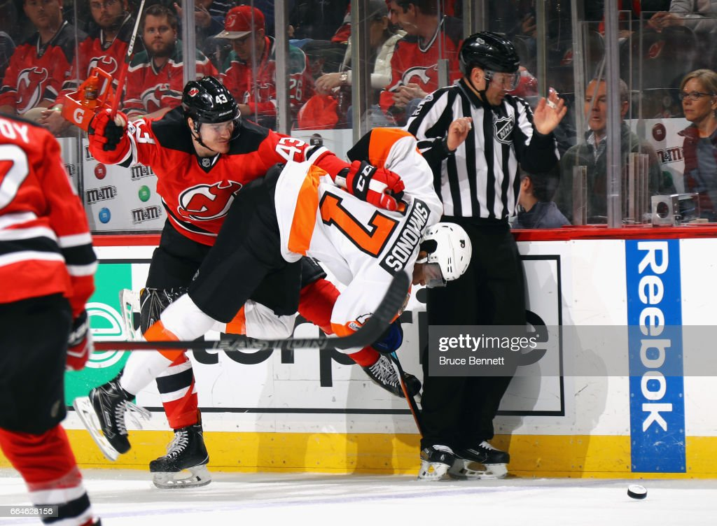 Playing in his first NHL game, Ben Thomson #43 of the New Jersey Devils hits Wayne Simmonds #17 of the Philadelphia Flyers during the first period at the Prudential Center on April 4, 2017 in Newark, New Jersey.