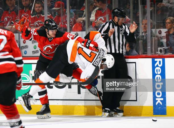 Playing in his first NHL game Ben Thomson of the New Jersey Devils hits Wayne Simmonds of the Philadelphia Flyers during the first period at the...