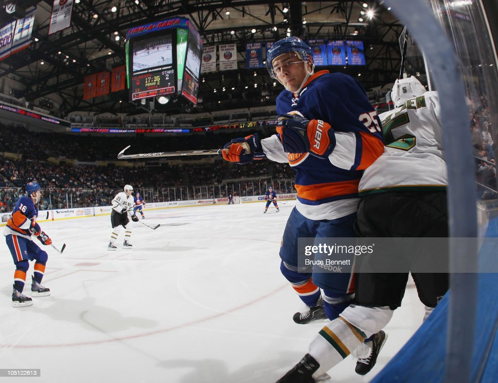 Playing in his first NHL game, <a gi-track='captionPersonalityLinkClicked' href=/galleries/search?phrase=Nino+Niederreiter&family=editorial&specificpeople=6667732 ng-click='$event.stopPropagation()'>Nino Niederreiter</a> #25 of the New York Islanders hits <a gi-track='captionPersonalityLinkClicked' href=/galleries/search?phrase=Matt+Niskanen&family=editorial&specificpeople=2106633 ng-click='$event.stopPropagation()'>Matt Niskanen</a> #5 of the Dallas Stars at the Nassau Coliseum on October 9, 2010 in Uniondale, New York.